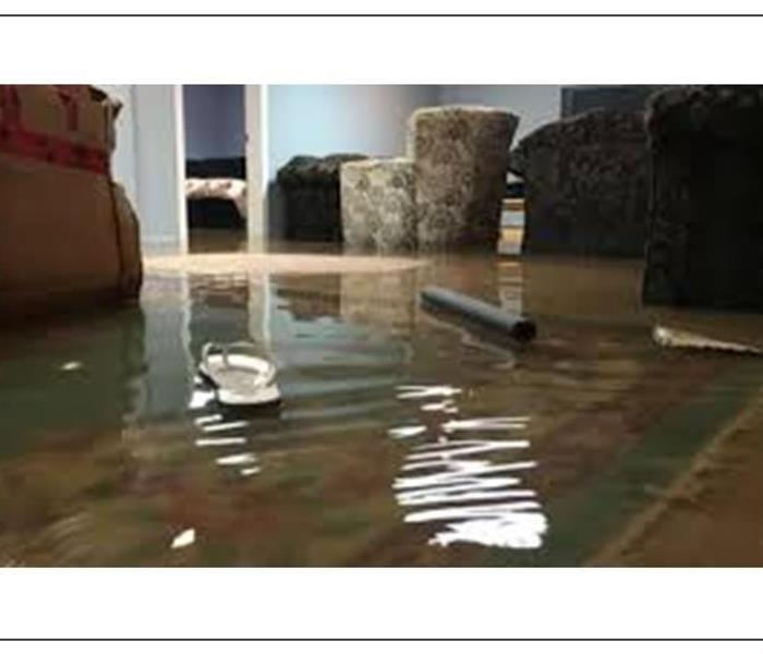 Picture of a flooded basement, showing furniture and carpet under water