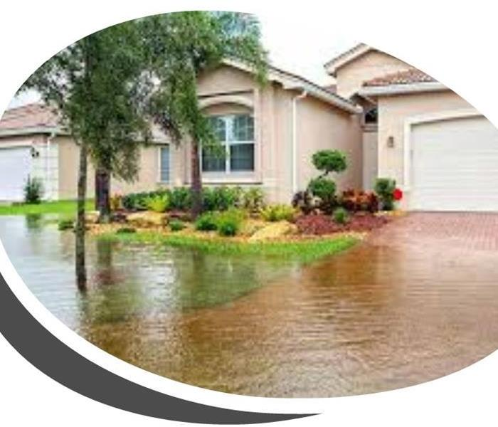This is an outdoor photo of the face of a home with a flooded driveway and front yard.