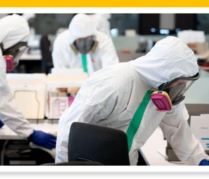 Image of cleaning technicians in full PPE wiping off desks in an office
